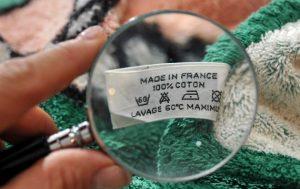 loupe où on voit une étiquette de vêtements avec écrit made in France